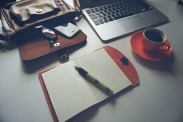 ordinateur stylo bloc note et café pour créer des sites de niche